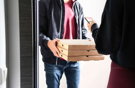 Pizza delivery to door. Online order with phone. Customer using smartphone mobile app to pay, tip or give rating and review. Home deliverer holding fast food boxes. Restaurant deliver service.