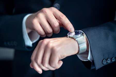 Watch around the wrist of a stylish business man. Busy businessman looking at the time. Stress or hurry at work. Person wearing suit and pointing at his wristwatch with finger. Deadline or overwork. 版權商用圖片