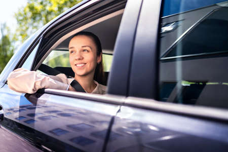 Woman in car as passenger on the backseat. Smiling female customer in taxi cab looking out the window. Happy elegant businesswoman with professional chauffeur driving. Fun city road trip.