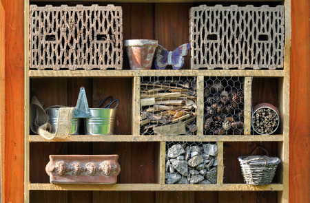 hibernate: Shelf with insect hotel and garden utensils Stock Photo