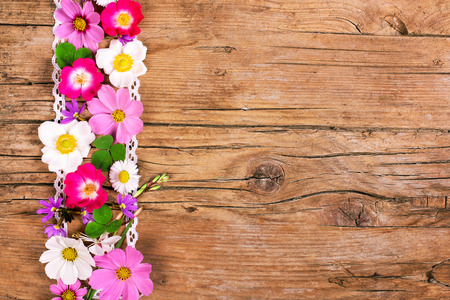 Flowers with lace, wooden background photo