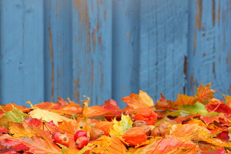 Wooden background with autumn foliage photo