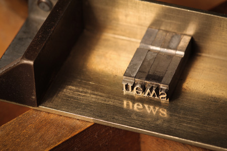 Composing stick with the letters news photo