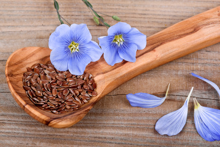 linseed oil: Wooden spoon with flaxseed and linum blossoms
