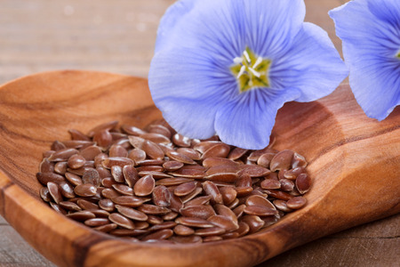 flaxseed: Wooden spoon with flaxseed and linum blossoms