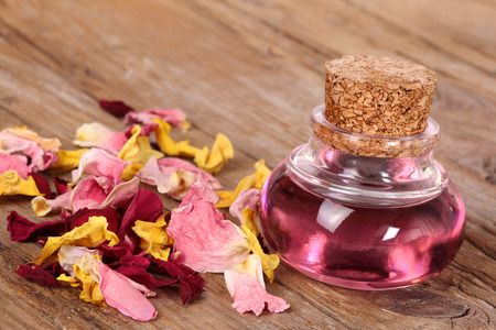 roses  petals: Glass flask with massage oil Stock Photo