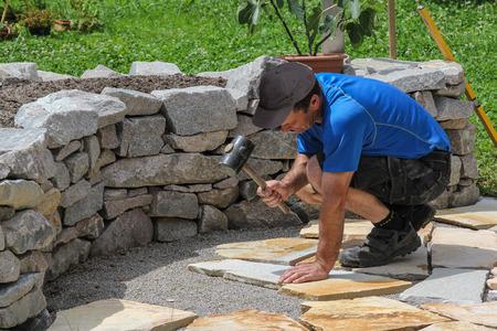 A worker laid tiles in the garden Foto de archivo