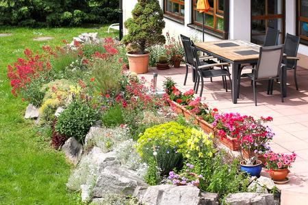 Terrace with garden furniture and rockery Standard-Bild