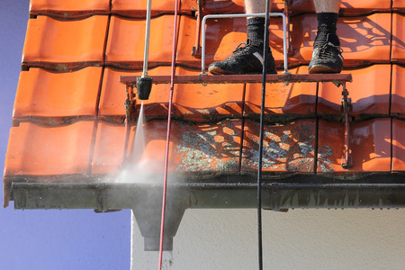 Roof and gutter cleaning with high pressure Stockfoto
