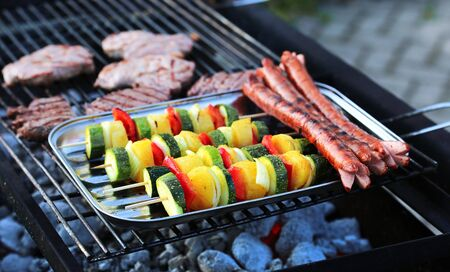 Vegetable skewers, sausages and steak on the grill