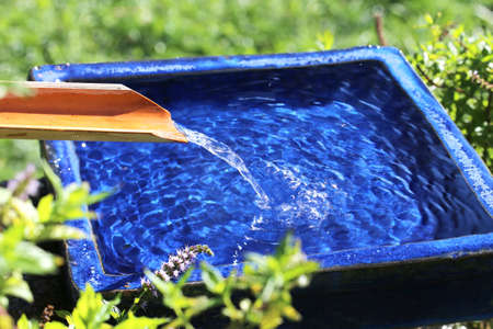 Water runs over a bamboo into a blue bowl Standard-Bild