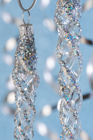 Silver christmas garland hanging on a ribbon on a blue background