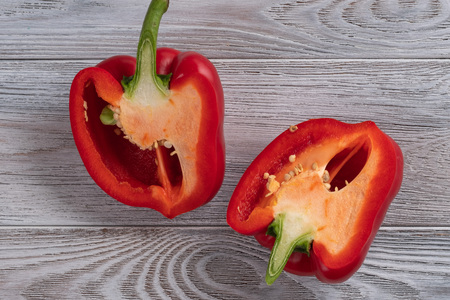 Healthy food. Red pepper cut in half close up on a wooden table