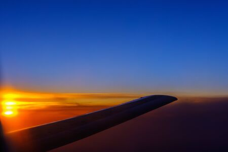 View of the sunset and the wing of the aircraft from the porthole during the flight Stock Photo