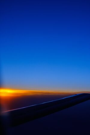 View of the sunset and the wing of the aircraft from the porthole during the flight 版權商用圖片