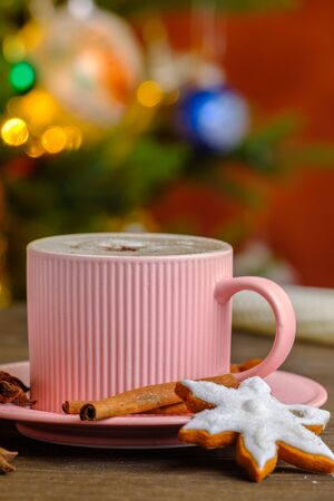 Cream coffee with christmas gingerbread on the background of the Christmas tree and lights Stock Photo