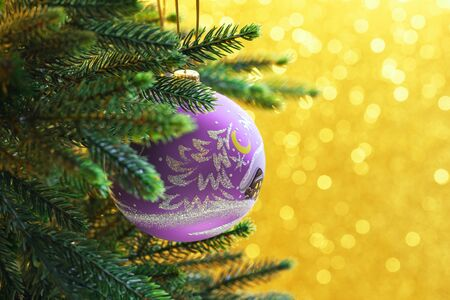 Lilac christmas balls on a gold background with bokeh Stock Photo