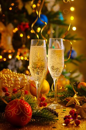Two glasses of champagne on the Christmas table on the background of Christmas trees