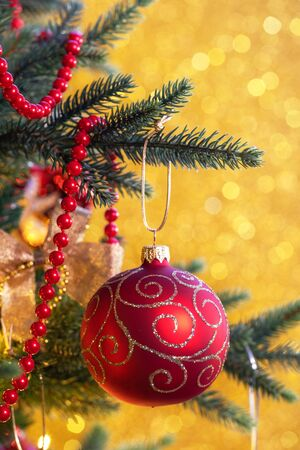 Red Christmas balls on a gold background with bokeh Stock Photo