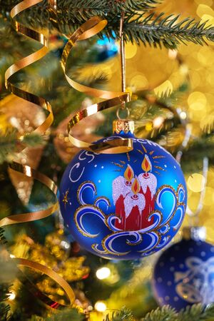 Blue Christmas balls on a gold background with bokeh