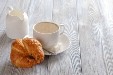 Delicious and crispy croissants with coffee on a white wooden table