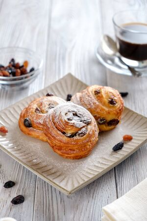 Breakfast with cup of coffee. Delicious and crispy croissants with coffee on a white wooden table Stock Photo