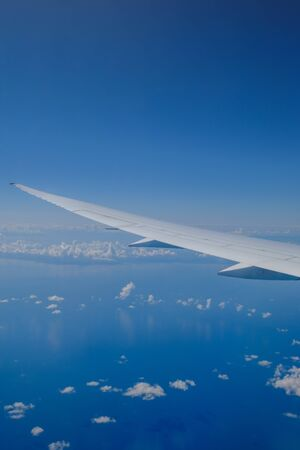View of the wing of the aircraft and the clouds from the porthole