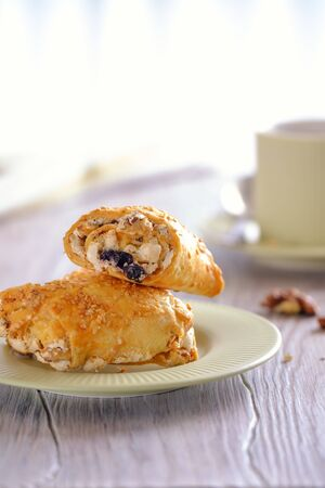 Homemade baking. Fresh and rouge rolls with nuts, raisins and meringues on a wooden table and a cup with aromatic coffee