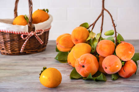 A branch of ripe persimmons on a wooden table against a background of a white brick wall