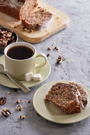 Delicious and flavorful banana cake with nuts and chocolate on a wooden board with a cup of coffee on a gray background