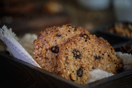 Delicious and flavorful oatmeal cookies with nuts, raisins and spices with a cup of milk on old wooden table