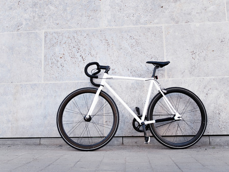bicyclette: Bicycle leaning against a stone wall on a street sidewalk in a healthy lifestyle concept Banque d'images