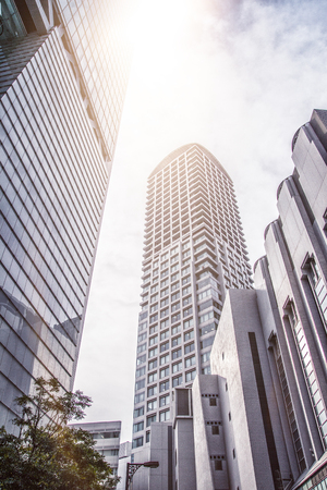 during the day: Low angle view of tall modern skyscrapers reaching into the bright sky during day Stock Photo