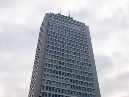 Low Angle Architectural Exterior View of Highrise Office Skyscraper Building with Generic Facade and Rooftop Transmission Towers with Cloudy Gray Sky in Background Editorial