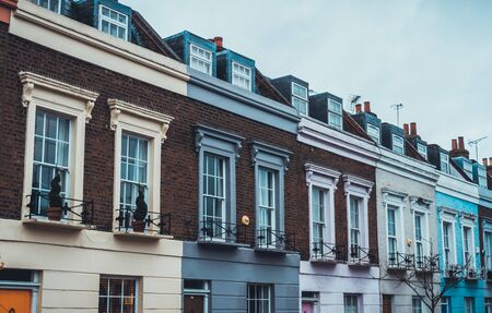 quaint: Architectural Exterior View of Stylish Luxury Apartments on Upper Floors of Quaint Row Houses Painted in Various Pastel Colors on Gloomy Gray Overcast Day