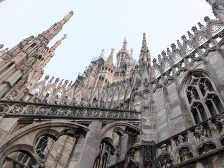 buttresses: Low Angle Architectural Close Up View of Historic Milan Cathedral Church with Focus on Decorative Flying Buttresses and Italian Gothic Style in Milan, Italy