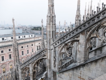 buttresses: High Angle Architectural Detail of Historic Milan Cathedral Church with Focus on Flying Buttresses and Italian Gothic Style - Overview of Hazy City from Roof of Cathedral, Milan, Italy