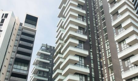 Panoramic Low Angle City View of Modern Residential High Rise Apartment Buildings with Wrap Around Balconies framed against Blue Sky