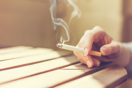 tip up: Close up view of the hand of a young woman smoking a recently lit filter tip cigarette sitting at a slatted wooden table, with copy space Stock Photo