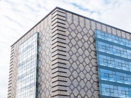 architectural exterior: Low Angle Architectural Exterior View of Modern Building with Decorative Pattern Facade and Floating Windows in front of Cloudy Blue Sky Editorial