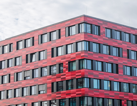 architectural exterior: Architectural Exterior of Modern Low Rise Building in Shades of Red with Large Windows on Overcast Day with Overhead Gray Clouds Editorial