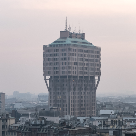 architectural exterior: Architectural Exterior View of Torre Velasca Skyscraper on Hazy Morning with Pastel Colored Sky in Milan, Italy