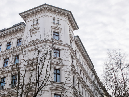 cornice: Low Angle Architectural Exterior View of Corner of White Building with Classic Design Features and Cornice and Surrounded by Bare Trees with Overcast Sky Overhead Stock Photo