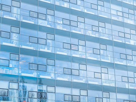 identical: Architectural Close Up of Modern Building with Glass Facade and Reflection of Sky and Trees in Windows, Identical Interior Details are Visible from the Outside Stock Photo