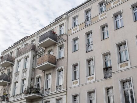 decorative balconies: Low Angle Architectural Exterior View of Luxury Residential Apartment Buildings with Decorative Facades and Small Balconies, Angled View with Cloudy Sky in Background