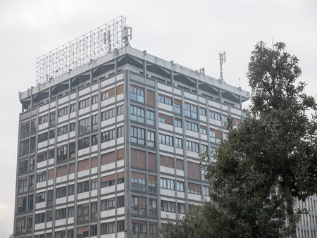 the antennae: Street level view of high rise apartment building with cellular telephone antennae on top