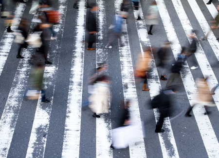 of movement: Group of pedestrians crossing the street at a zebra crossing with motion blur to the people and focus to the markings on the road, high angle view