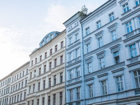 architectural exterior: Low Angle Architectural Exterior View of Urban Low Rise Buildings with Classic Design Features with Light Blue Apartment in Foreground on Day with Blue Sky and Copy Space Stock Photo