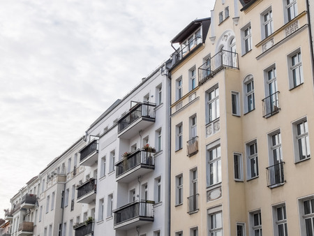 angled view: Low Angle Architectural Exterior View of Modern Residential Apartment Buildings with Small Balconies and Plain Facades, Angled View with Cloudy Overcast Sky in Background