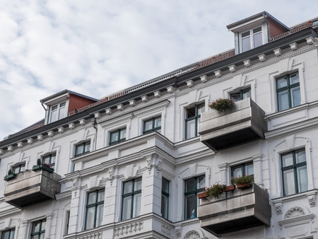 decorative balconies: Low Angle Architectural Exterior View of Luxury Residential Apartment Building with Small Balconies and White Facade and Cloudy Sky in Background